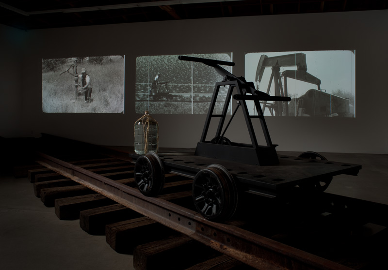 "Pumping is an art installation by Joel Tauber that imagines a future when water is scarce and oil no longer exists; while it also looks back at the forces that built the sprawling city of Los Angeles. It is comprised of three video projections; and also includes, in its most complete form: train tracks, a giant metal ""filmstrip"", a series of photographs, and a handcar sculpture."