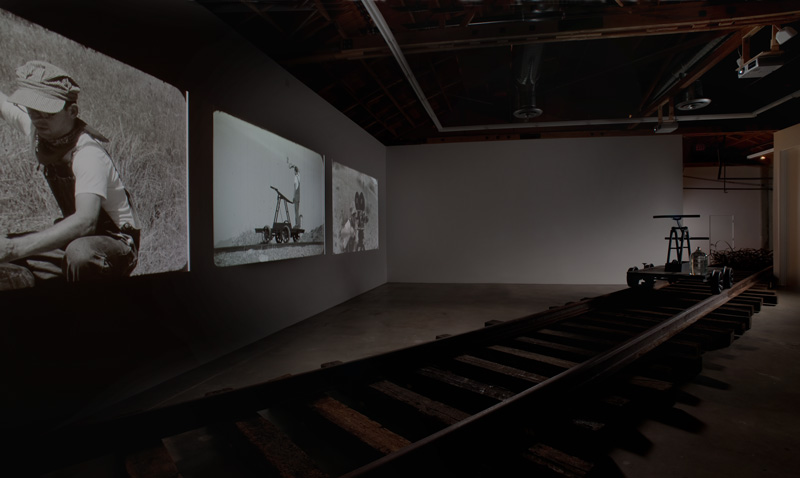 """Pumping is an art installation by Joel Tauber that imagines a future when water is scarce and oil no longer exists; while it also looks back at the forces that built the sprawling city of Los Angeles. It is comprised of three video projections; and also includes, in its most complete form: train tracks, a giant metal """"filmstrip"""", a series of photographs, and a handcar sculpture."""